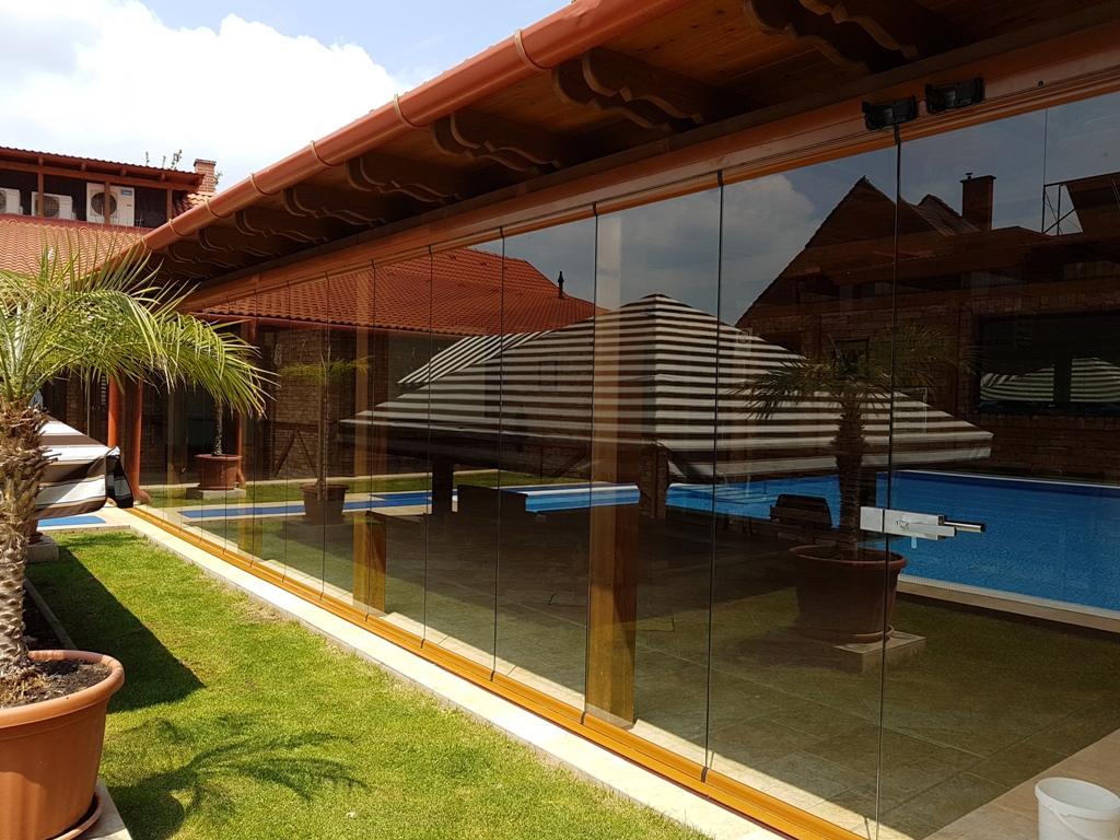 Terasz beépítése lapozható üvegfallal nagy felületen, íves elemekkel